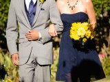 a navy strapless bridesmaid dress, a grey suit with a navy tie and yellow blooms