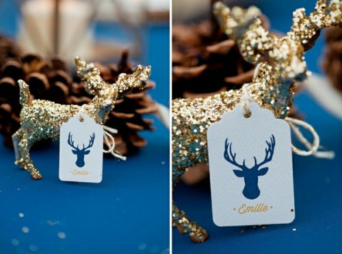 a navy tablecloth, a gold glitter deer and pinecones for a winter wedding