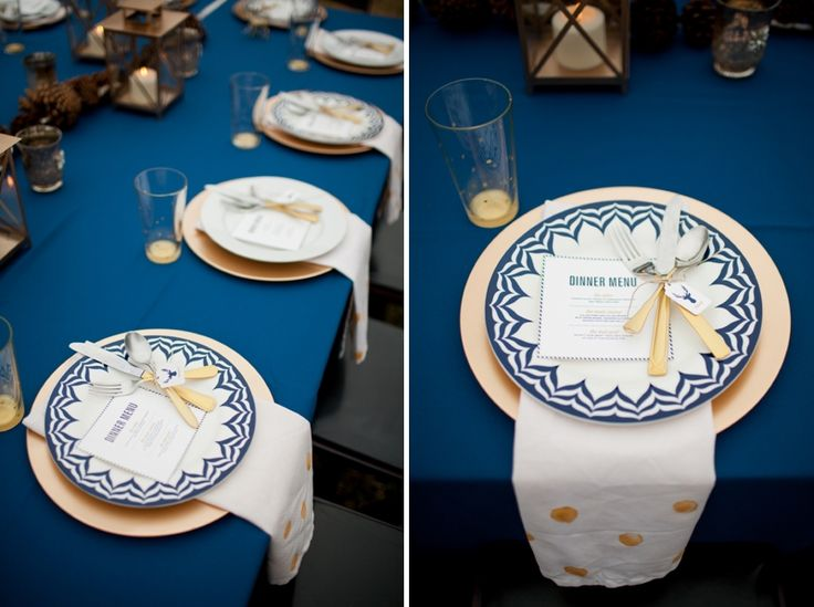 a navy, gold and white wedding tablescape with candle lanterns and pinecones