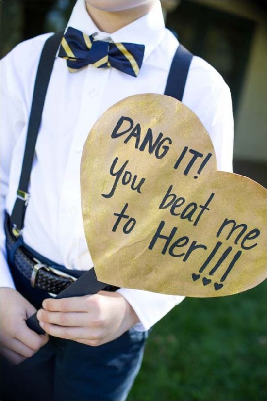 a ring bearer dressed in navy and white and with a gold and navy heart