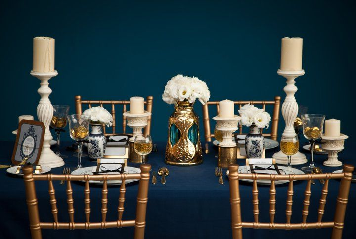 a navy, gold and white wedding tablescape with candles and lush white bloom centerpieces