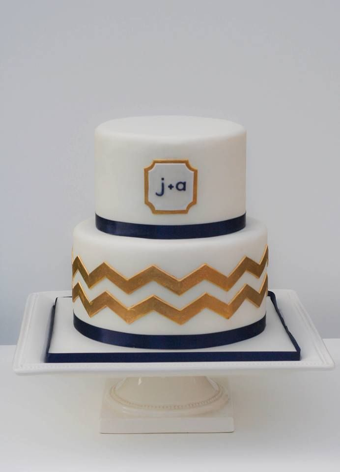a chic white, navy and gold wedding cake with a timeless chevron pattern