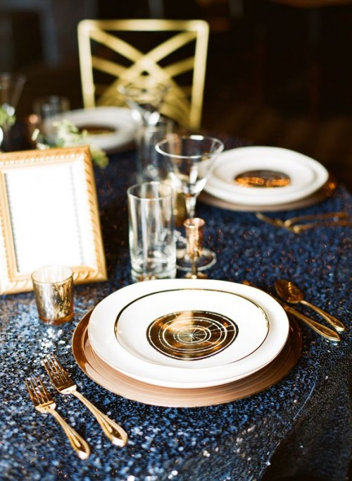 a bold navy glitter and gold tablescape with nautical touches and candles