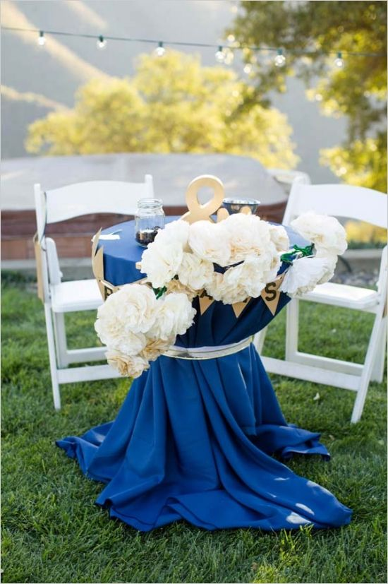 a navy cocktail table with white lush blooms and gold buntings and accessories