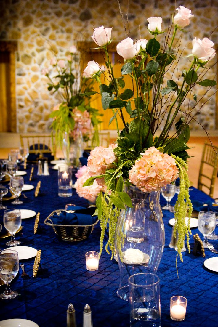 a chic navy tablescape with gold touches, candles and lush floral centerpieces