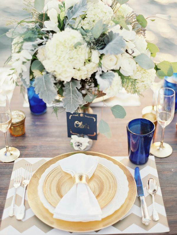 a chic place setting with a chevron placemat, a gold and white setting, blue glasses and vases and a lush centerpiece