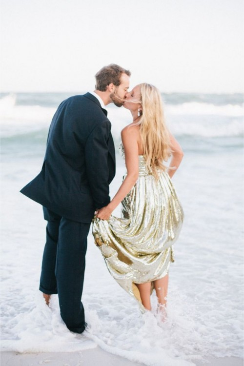 the groom wearing a navy suit, the bride wearing a gold sequin strapless gown