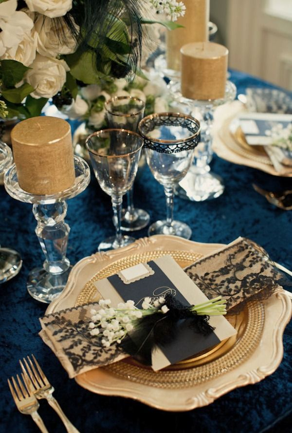 a navy, gold and white tablescape, candles, gold rim glasses and a setting with lace