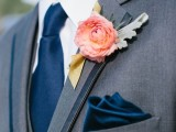 a grey suit with navy accessories and a single coral bloom boutonniere