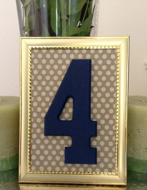 a navy table number in a gold frame with a polka dot backdrop