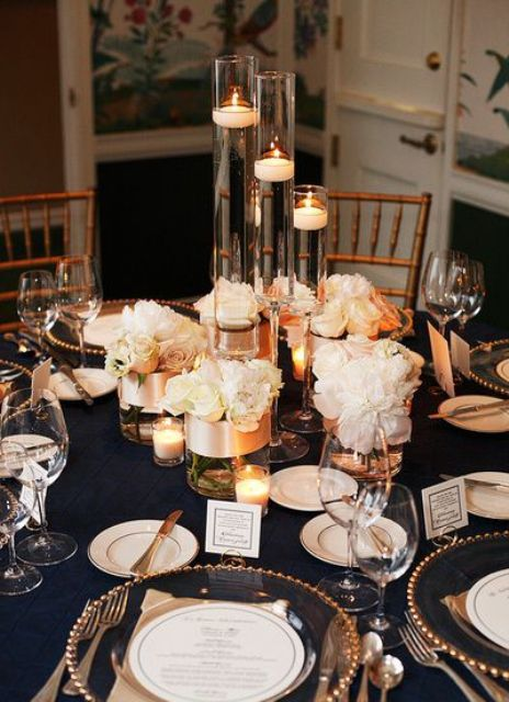a chic navy, gold and creamy wedding tablescape with candles, white floral centerpieces and a sheer charger