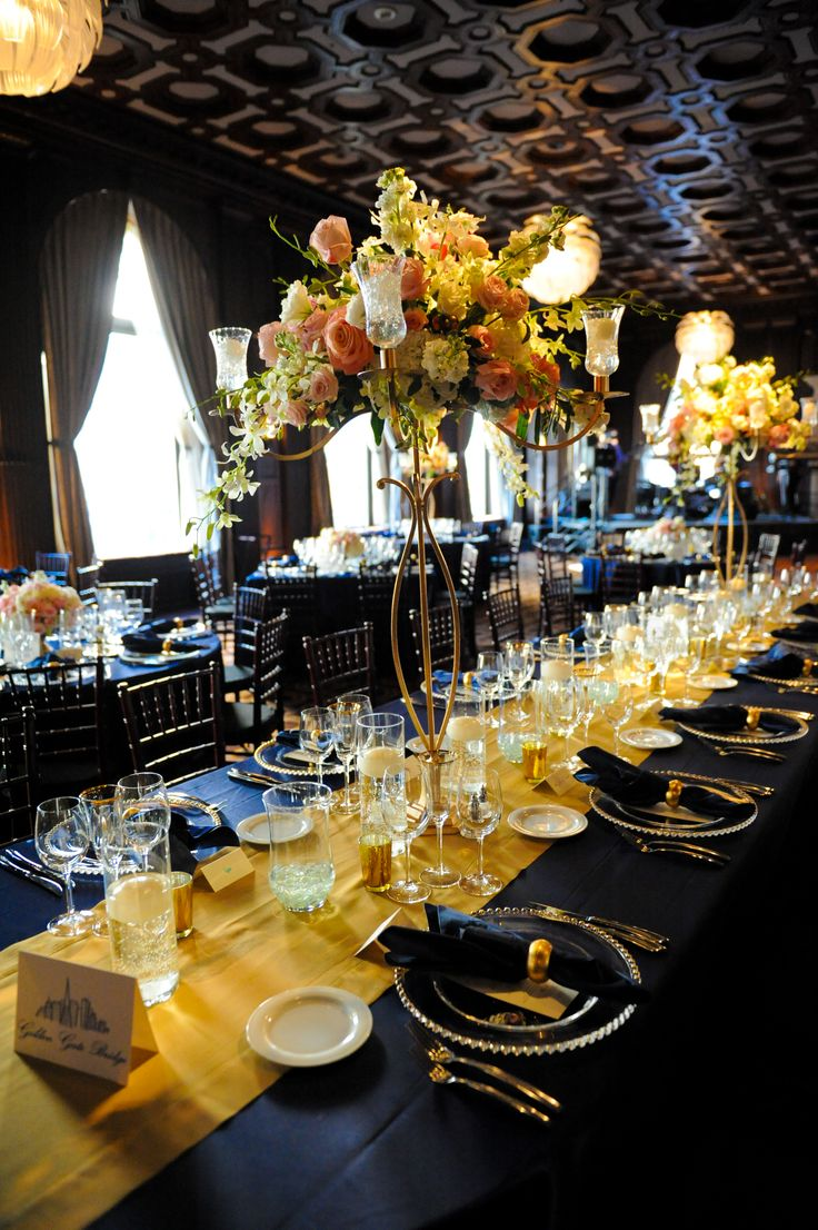 a navy and gold wedding table setting with lush floral centerpieces, sheer chargers, gold candle holders