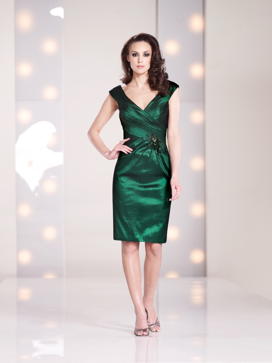 a stylish emerald fitting knee dress with a V neckline, cap sleeves and a draped bodice plus an embellishment on the waist