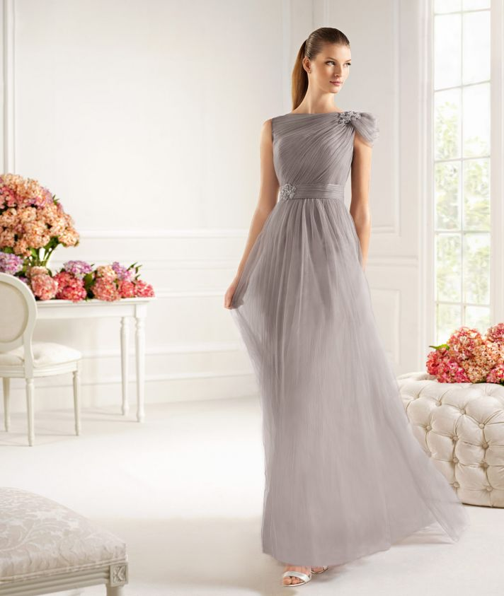 an airy grey draped A line maxi dress with a single cap sleeve and silver shoes for a very elegant a chic mother of the bride look