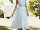 a lace strapless A-line tea length wedding dress with cap sleeves, a blue sash, pearls and peep toe wedding shoes