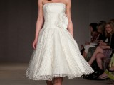 a strapless A-line tea length wedding dress with a large fabric bloom, silver shoes and a pearl necklace is very chic