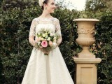 a lace A-line tea length wedding dress with an illusion neckline and short sleeves, white shoes and a blush fabric headpiece