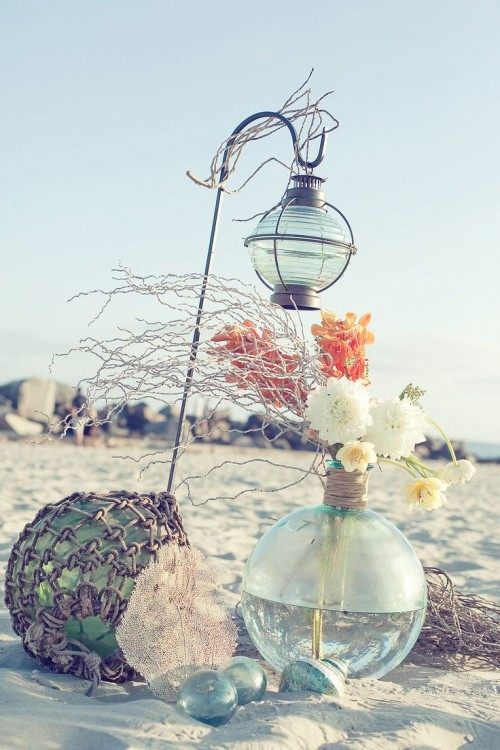beach bridal shower decor with floats, a large float vase with blooms and branches and net covering the float