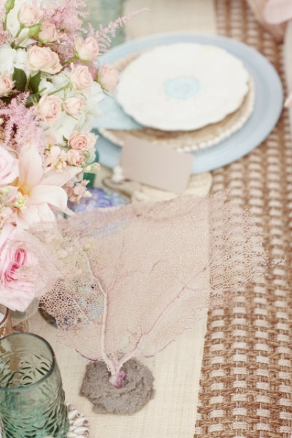 elegant beach bridal shower decor with a wicker table runner, blue and tan plates, corals and pink blooms