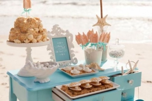 a blue dessert table with various sweets and cakes styled for a beach bridal shower is perfect for your party