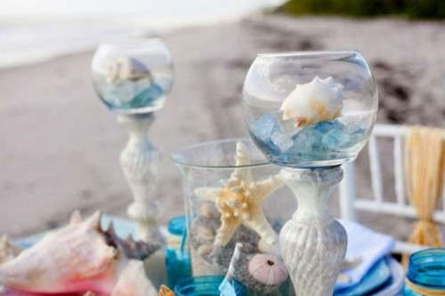 jars with sand and blue stones and seashells are great to create a mood and a chic look at the beach bridal shower table