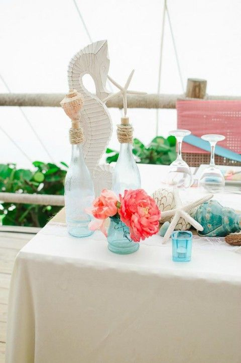a chic beach bridal shower table done with turquoise glasses, seashells, starfish, bright blooms, a white sea horse decoration