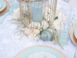 a pastel ethereal bridal shower tablescape with white and blue linens, a cage with a blue candle, white blooms, seashells and blue plates looks veyr beautiful