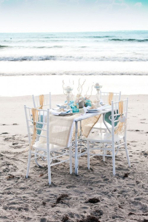 a beach bridal shower tablescape done with driftwood, corals, starfish, seashells and bright touches of turquoise
