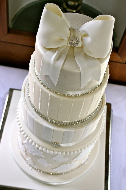 a glam white wedding cake with plain and striped tiers, with rhinestones and an oversized bow on top