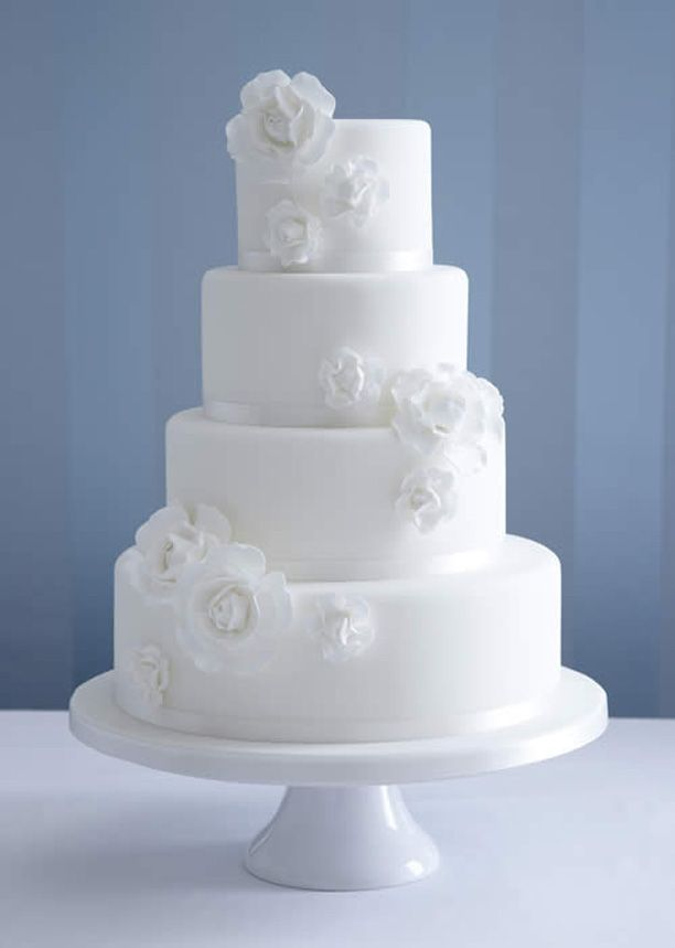 a white wedding cake decorated with white sugar blooms is a timeless dessert for an elegant wedding