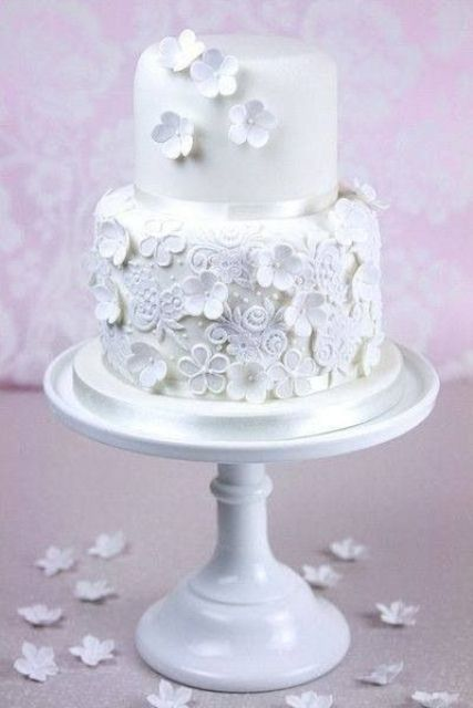 a white wedding cake decorated with edible blooms and lace is a stylish dessert for a modern romantic wedding