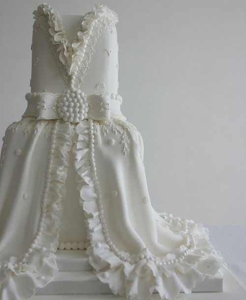 a unique wedding cake styled as a vintage wedding dress with edible detailing and embellishments is a fantastic idea