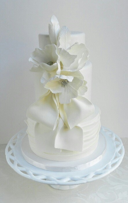 a white textural wedding cake decorated with white sugar bloms and bows is a romantic and refined dessert