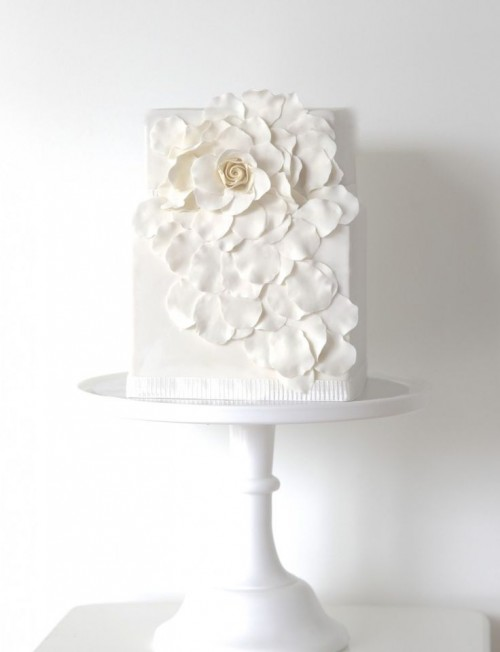 a square wedding cake decorated with a large whiet sugar bloom and petals is a lovely and chic idea
