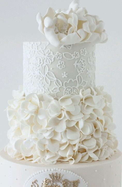a white patterned wedding cake with a ruffle tier, large sugar blooms is a stylish refined idea for a glam wedding