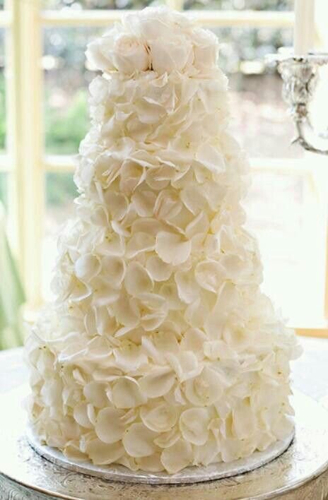 a white wedding cake decorated with white sugar blooms and with natural white roses on top is a chic idea