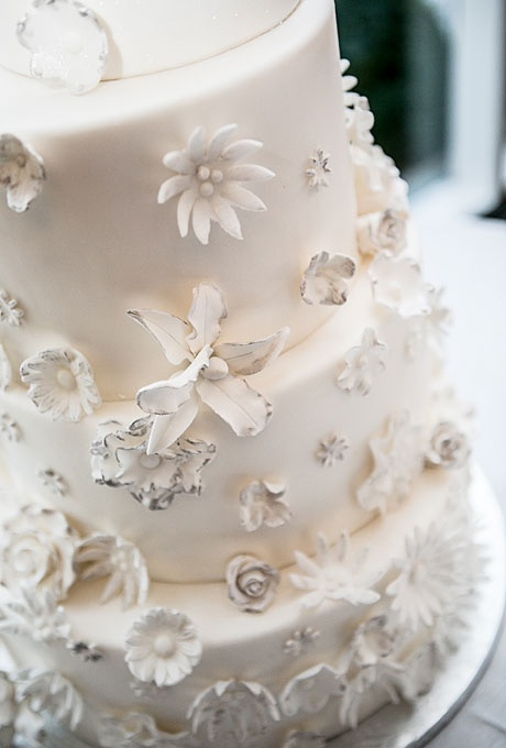 a white wedding cake decorated with white and black edible blooms is a very chic and stylish idea