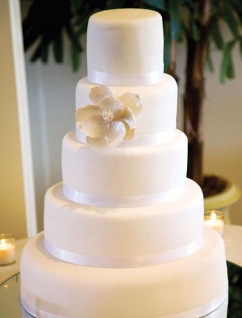 a timeless white wedding cake with ribbons and a large sugar bloom is an elegant dessert for your wedding