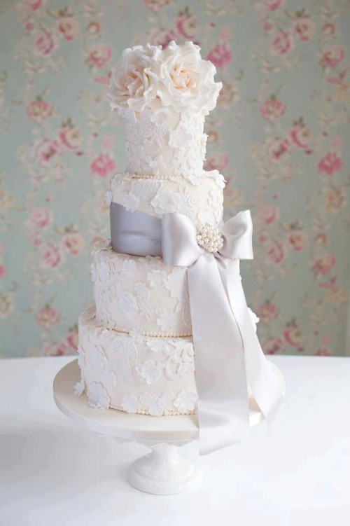 a neutral wedding cake with white sugar blooms, a large bow with a brooch and blush natural blooms on top