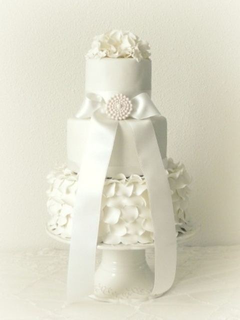 a white wedding cake with plain and a ruffle tier, with a large ribbon bow and a brooch, white sugar blooms on top