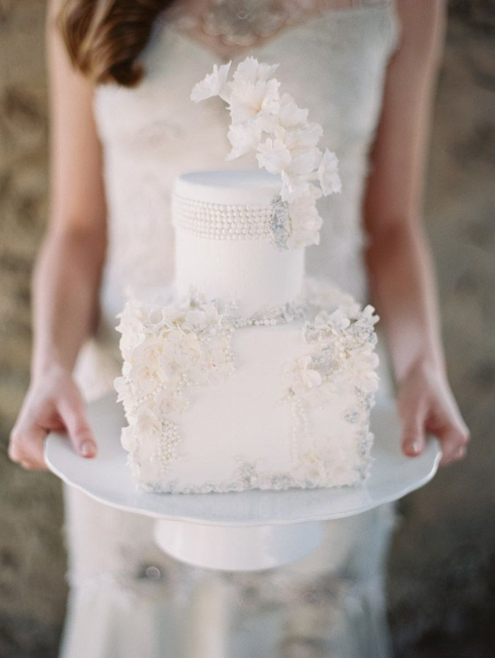 a refined round and square wedding cake decorated with neutral sugar blooms and beads is a stylish and cool idea