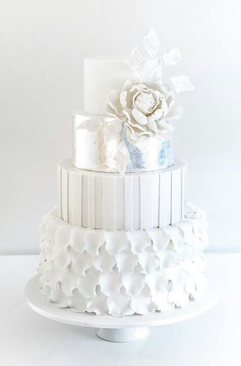 a white wedding cake with a petal, stripe and plain tier, with a silver one, sugar blooms and leaves