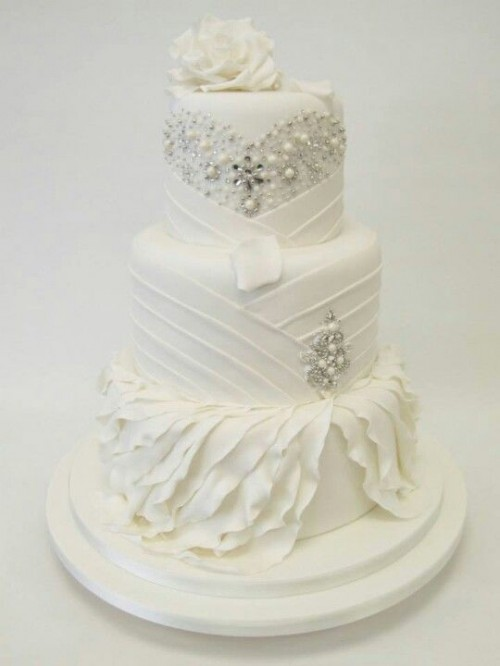 a white wedding cake with patterns, embellishments, pearls and a a white bloom on top