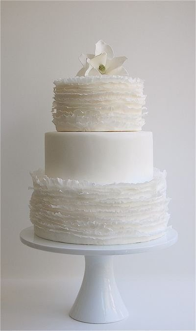 a white wedding cake with ruffle and plain tiers, a white sugar bloom on top is a chic and stylish dessert to rock