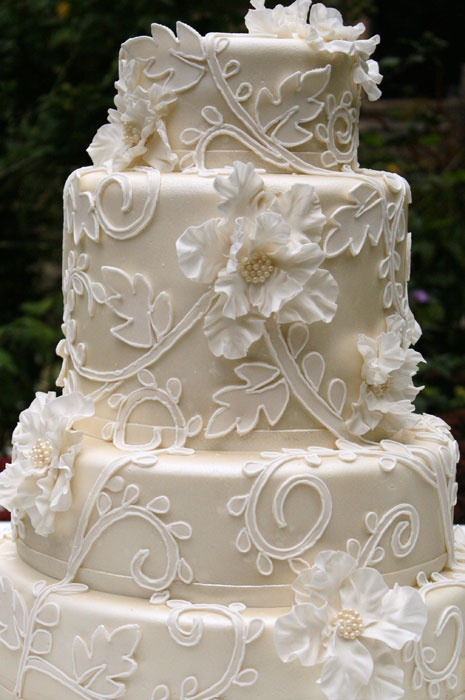 a tan wedding cake with white floral patterns and leaves, with white sugar blooms is a nice fit for a refined wedding