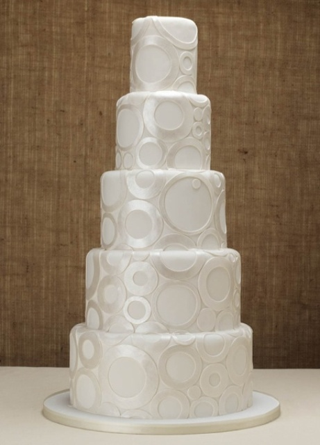 a white wedding cake decorated with shiny metallic circles is a stylish idea for a modern wedding