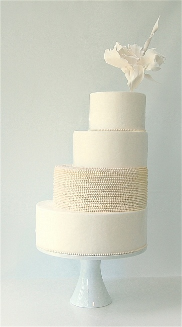a charming white wedding cake with plain and beaded tiers and a large sugar bloom on top