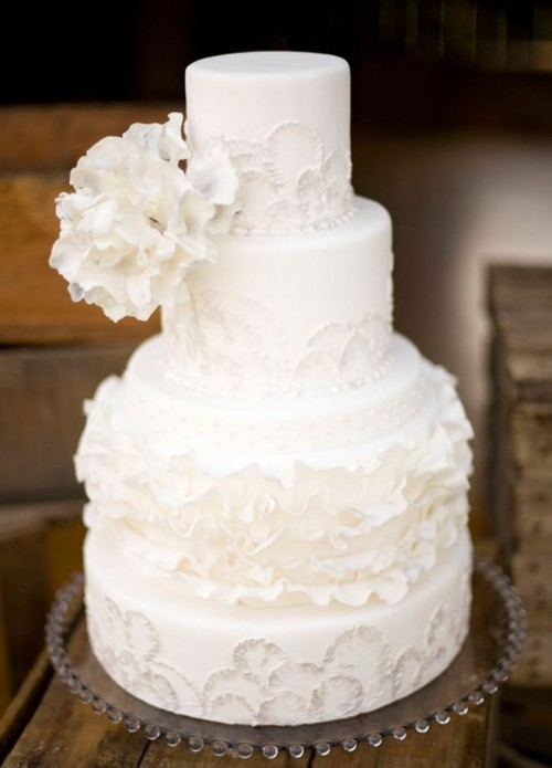a refined white patterned wedding cake with floral and ruffles patterns and oversized white sugar blooms on top