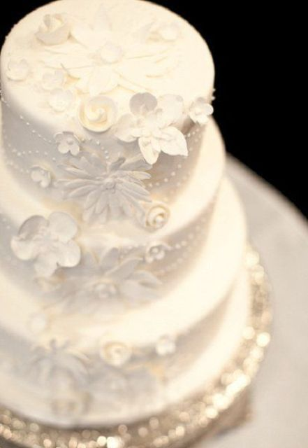 a white patterned wedding cake decorated with beads and sugar blooms is a very romantic vintage-inspired piece