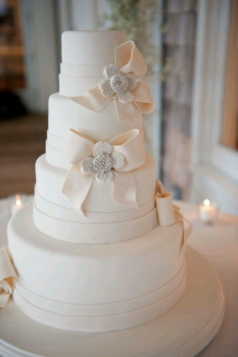 an elegant white wedding cake decorated with edible bows and rhinestones is a very chic and refined piece